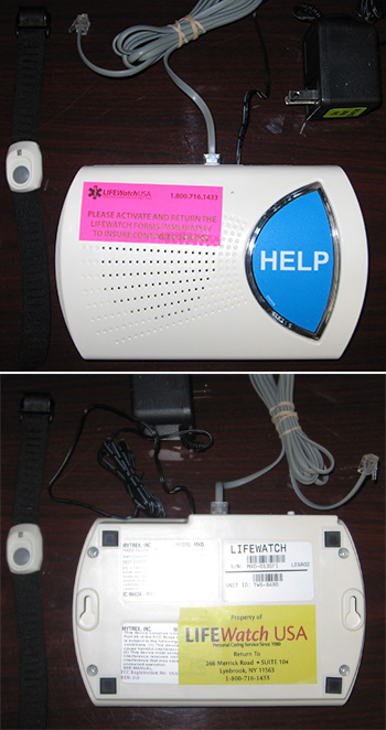 Life Watch alert device, top and bottom views, with accompanying power adapter, telephone cable, and wristband. Top of device has a large blue button labeled help and a pink LifeWatchUSA activation instruction label. Bottom has a yellow label 'Property of LifeWatchUSA' with address in Lynbrook, New York