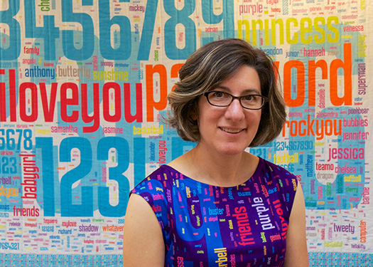 author wearing a multicolored dress with common passwords on it, in front of a large quilt with the same theme