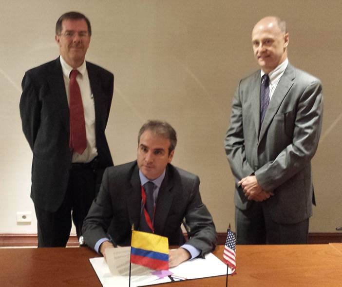 Pablo Felipe Robledo (seated), Colombia's Superintendent of Industry and Commerce, signs the MOU with Russell Damtoft, Associate Director, FTC Office of International Affairs and Caldwell Harrop, Dept. of Justice looking on.